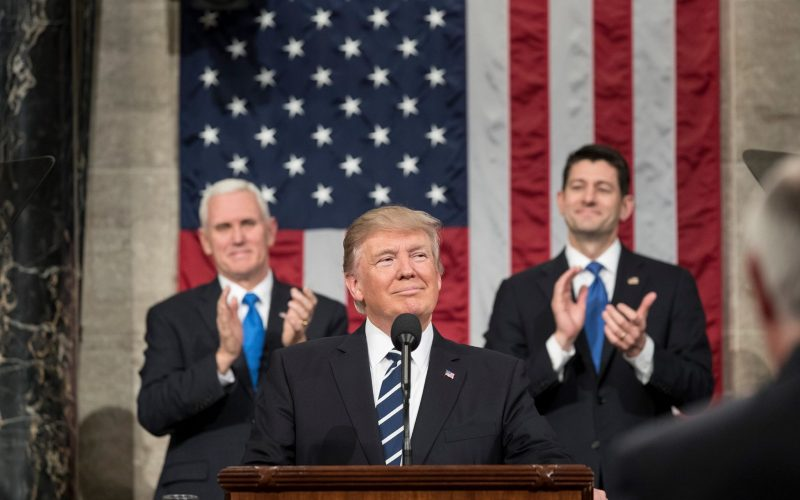 an image of President Donald Trump standing at a podium with Vice President Mike Pence and Speaker Paul Ryan standing in front of an American flag behind him